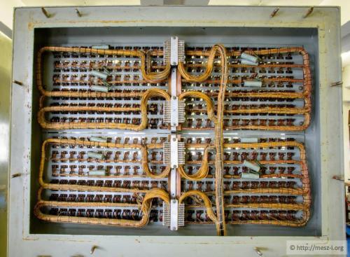 Az egyik szekrény felső fele hátulról, jól látszik az összetett kábelezés